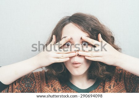 girl looking through fingers