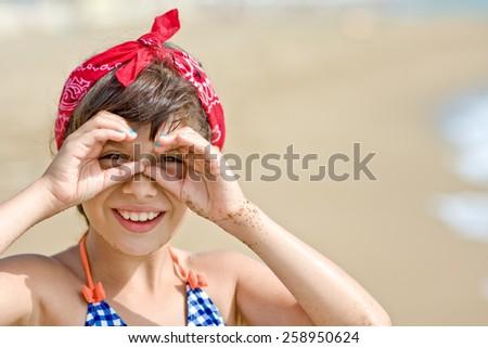 Girl looking through imaginary binocular on beach - stock photo
