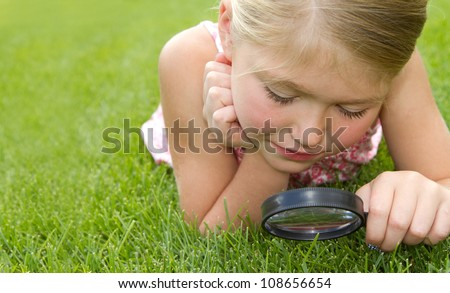 girl looking through magnifiying glass at grass outdoors