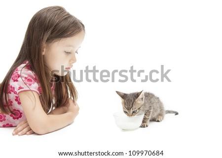 girl looking to kitten  - eating  milk - stock photo