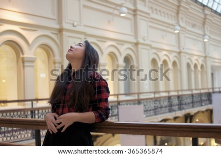 Girl looking up on the balcony and leaning on the railing - stock photo