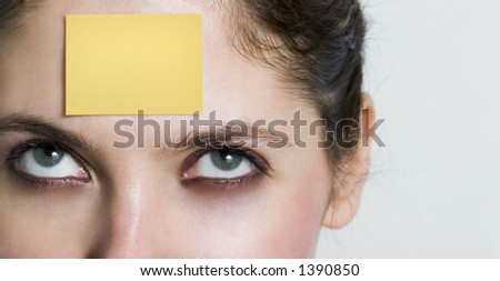 girl looking up to a yellow post it sticked on her forehead. You can write whatever you want over it... - stock photo