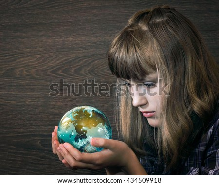 Girl looks at a glass ball in the hands of