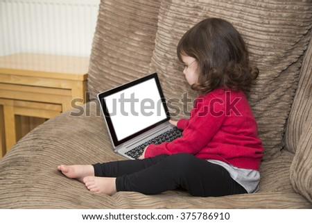Girl looks at computer screen - stock photo