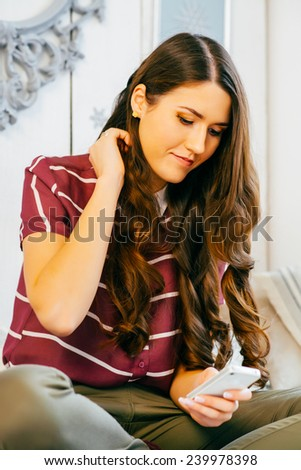 girl looks at the phone sitting on the sofa - stock photo