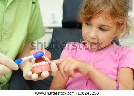 Girl looks how to correctly brush teeth. For clarity, doctor uses artificial jaw. - stock photo