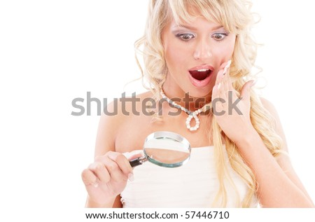 Girl looks in magnifier and is surprised, isolated on white background.