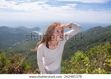 girl looks into the distance from the top of the mountain - stock photo