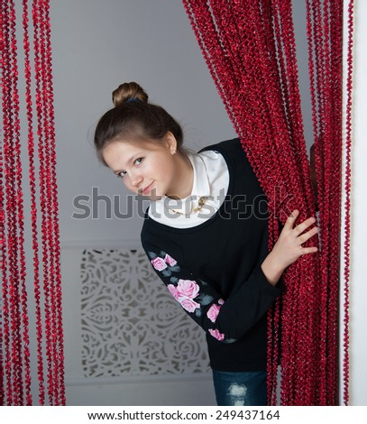 girl looks out from behind the curtain - stock photo