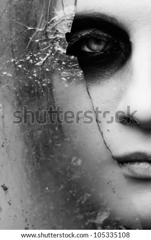 Girl looks through broken glass - stock photo