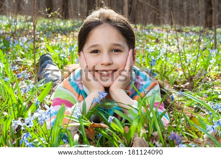 Girl lying among the bluebells in the spring forest
