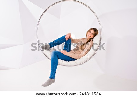 Girl lying and rests in a transparent glass chair against a white wall with geometric shape.  Beautiful girl with with pigtail smiling - stock photo