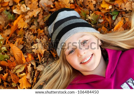 girl lying down on autumn leaves birds eye view - stock photo