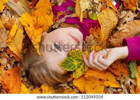 girl lying down on autumn leaves birds eye view