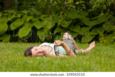 Girl lying down on grass in the park - stock photo