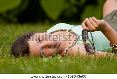Girl lying down on grass in the park and holding sunglasses - stock photo