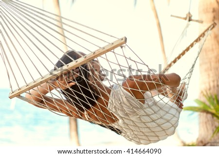 girl lying in a hammock under the palm trees on the island - stock photo