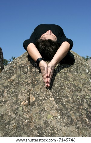 girl lying in a rock in moment of relax, meditation or faith