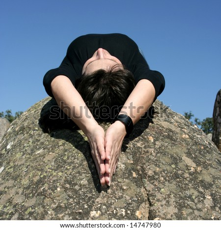 girl lying in a rock in moment of relax, meditation or faith - square format