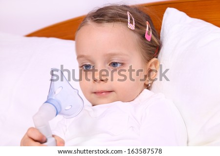 Girl lying in bed and looking at a device aerosol mask - stock photo