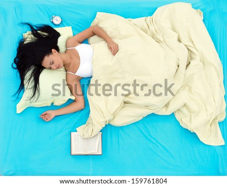 Girl lying in bed and sleeping after reading a book, view from above - stock photo