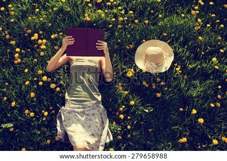 Girl lying in grass, reading a book. Intentionally toned. - stock photo