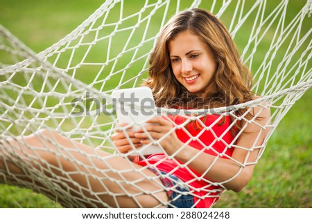 Girl lying in hammock and using digital tablet - stock photo