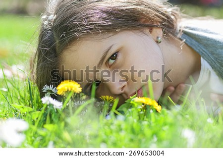 Girl lying in the grass surrounded with white flowers