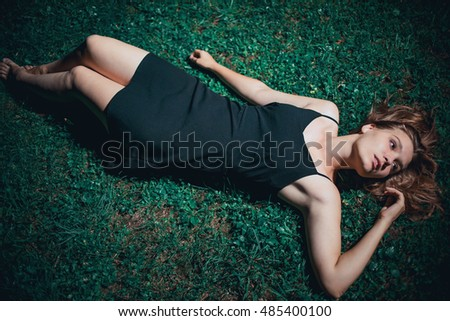Girl lying in the night on the grass