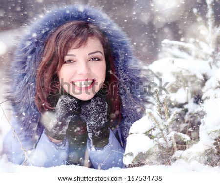 girl lying in the snow under the Christmas tree