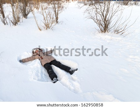 Girl lying in the snow. Winter in the city park.