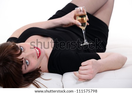 Girl lying on a couch with glass of champagne - stock photo