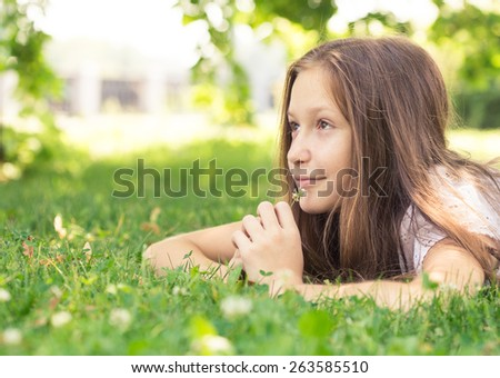 girl lying on a grass and holding a flower  - stock photo