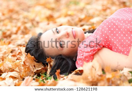 girl lying on autumn maple leaves - stock photo