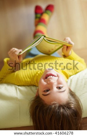 girl lying on bed and reading book - stock photo