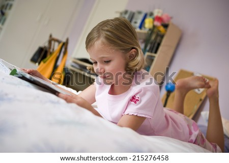 Girl (6-8) lying on bed, reading book, side view, surface level (tilt) - stock photo