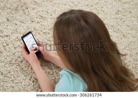 Girl Lying On Carpet Checking Message On Mobile Phone - stock photo