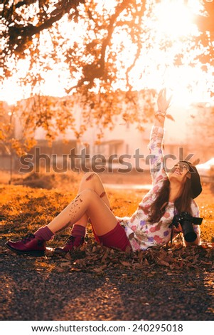 girl lying on grass at sunset holding a camera on one hand and raising her other hand to air - stock photo