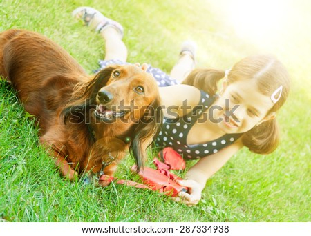 Girl lying on grass with a dachshund dog - stock photo