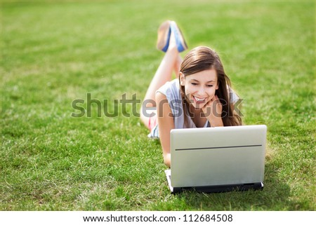 Girl lying on grass with laptop - stock photo