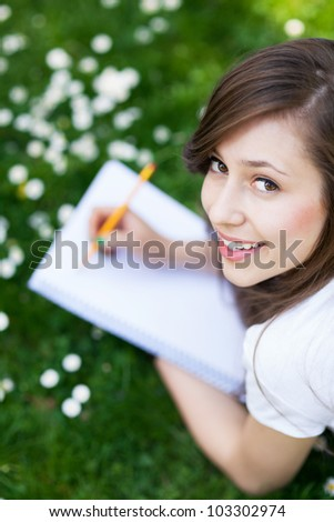 Girl lying on grass with workbook - stock photo