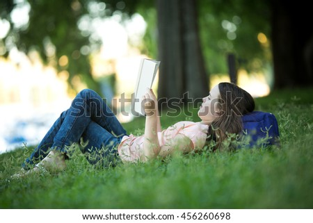 Girl lying on green grass outdoors in summer or spring reading a white book wearing jeans - stock photo