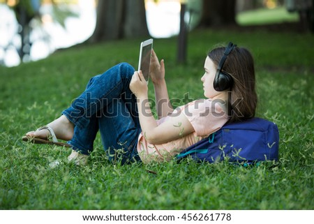 Girl lying on green grass outdoors in summer or spring reading her ipad or tablet and wearing headphones