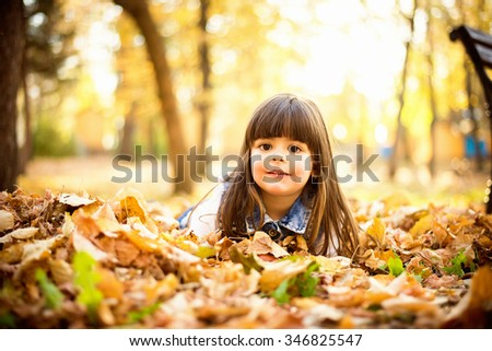 Girl lying on leaves Beautiful little girl lying on autumn leaves in the park,smiling and having fun