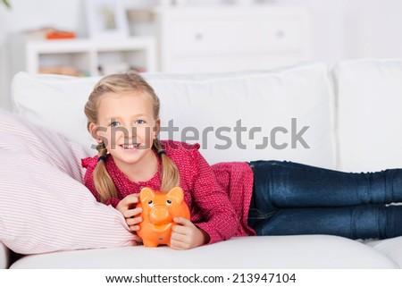 girl lying on sofa holding piggy bank in her hand - stock photo