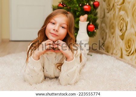Girl lying on the carpet, looking at the camera and smiling. A child in a warm white sweater. Christmas tree. Teen in New Year clothes. - stock photo