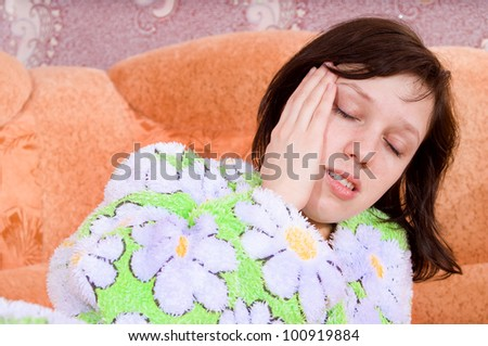 girl lying on the couch and her head hurts - stock photo