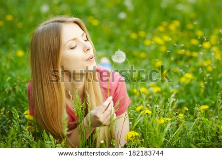 Girl lying on the field of dandelions blowing dandelion, wish concept - stock photo