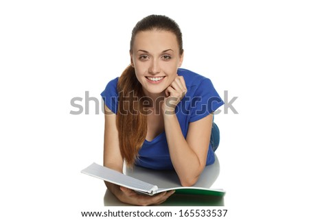 Girl lying on the floor with an open notebook and smiling.
