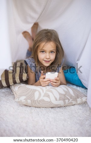 Girl lying on the front and using a mobile phone - stock photo